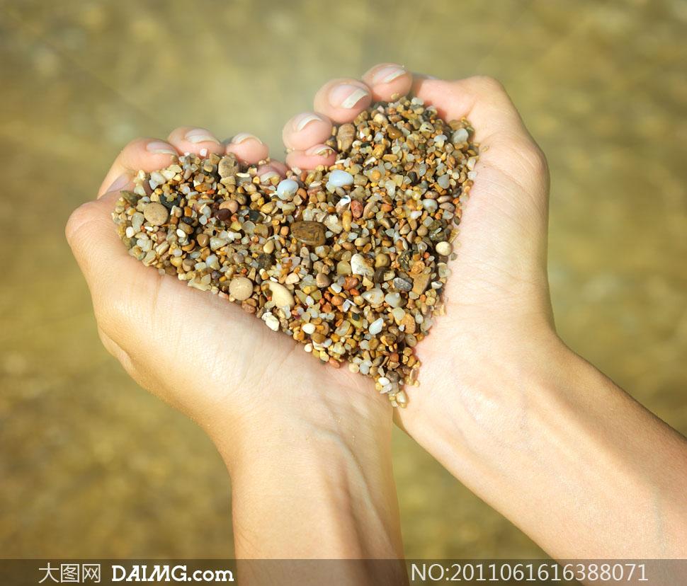 双手捧起心形碎石子高清摄影图片