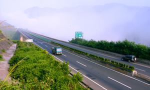 大雾笼罩下的大山与公路高清摄影图片