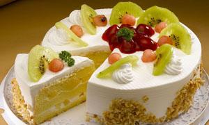 切开一角的水果生日蛋糕摄影图片