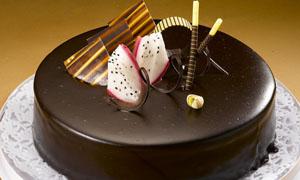 插着巧克力和水果的蛋糕摄影图片
