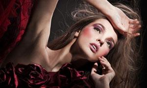 手抚摸着头部的时尚女性高清图片