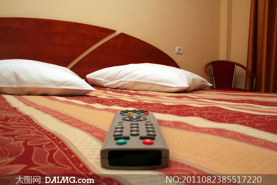 卧室房间床上的遥控器高清摄影图片