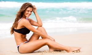 海边沙滩上坐着的比基尼美女高清摄影图片