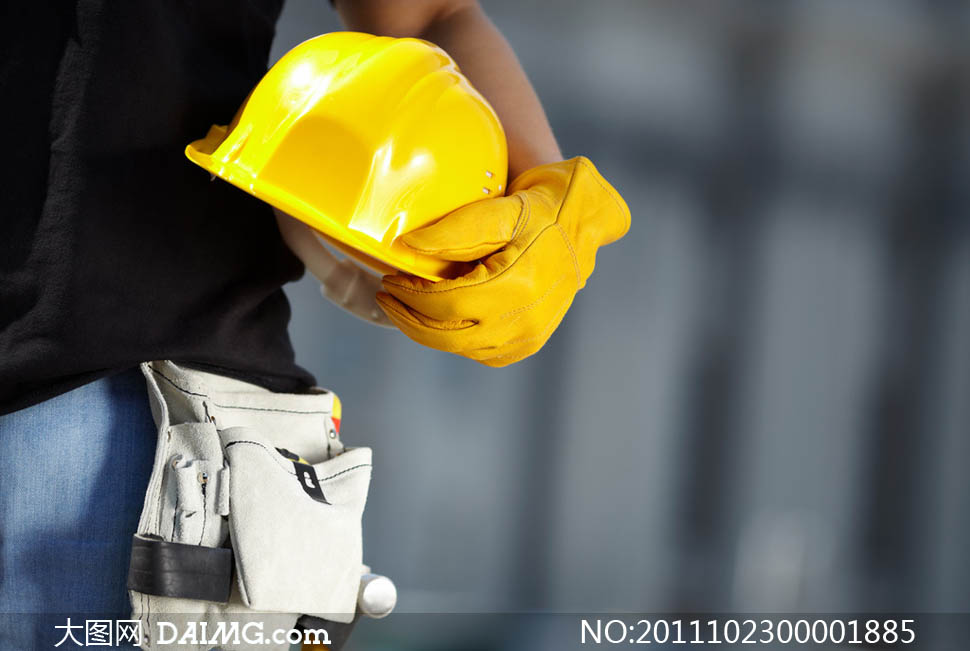 建筑工人腰间拿着帽子摄影图片
