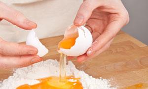 往面粉里打鸡蛋的情景高清摄影图片
