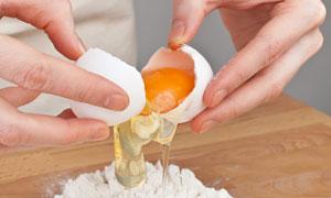双手打鸡蛋与案板上的面粉高清摄影图片
