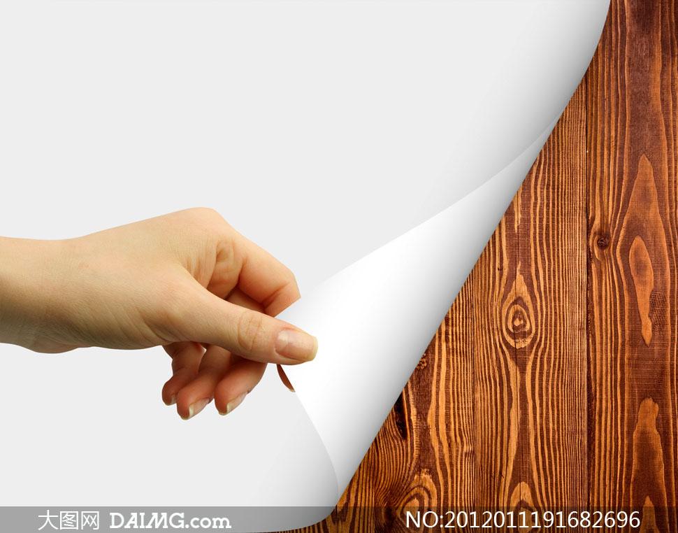木板上的白纸掀起一角高清摄影图片