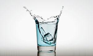 杯子中淡蓝色液体飞溅效果与冰块摄影图片