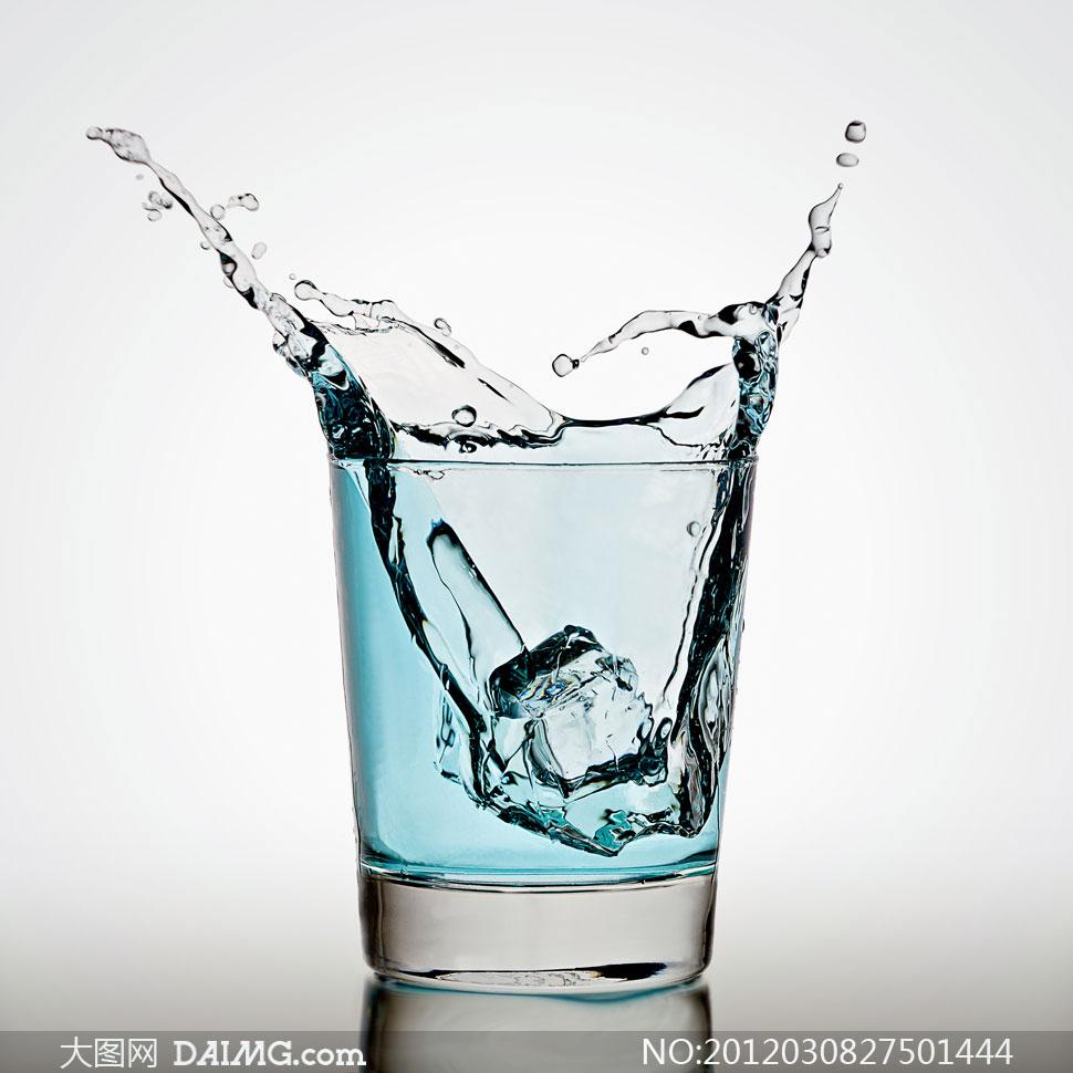 杯子中淡蓝色液体飞溅效果与冰块摄影图片图片