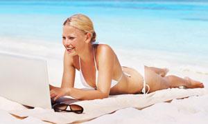 沙滩上趴着玩电脑的美女高清摄影图片