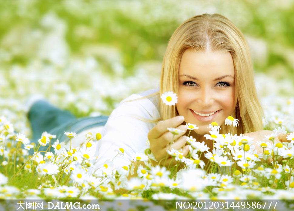 趴在雏菊花丛中的外国美女高清摄影图片