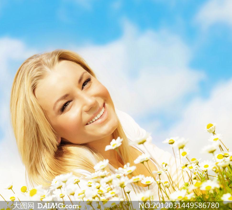 歪头侧躺在花丛中的美女人物高清摄影图片