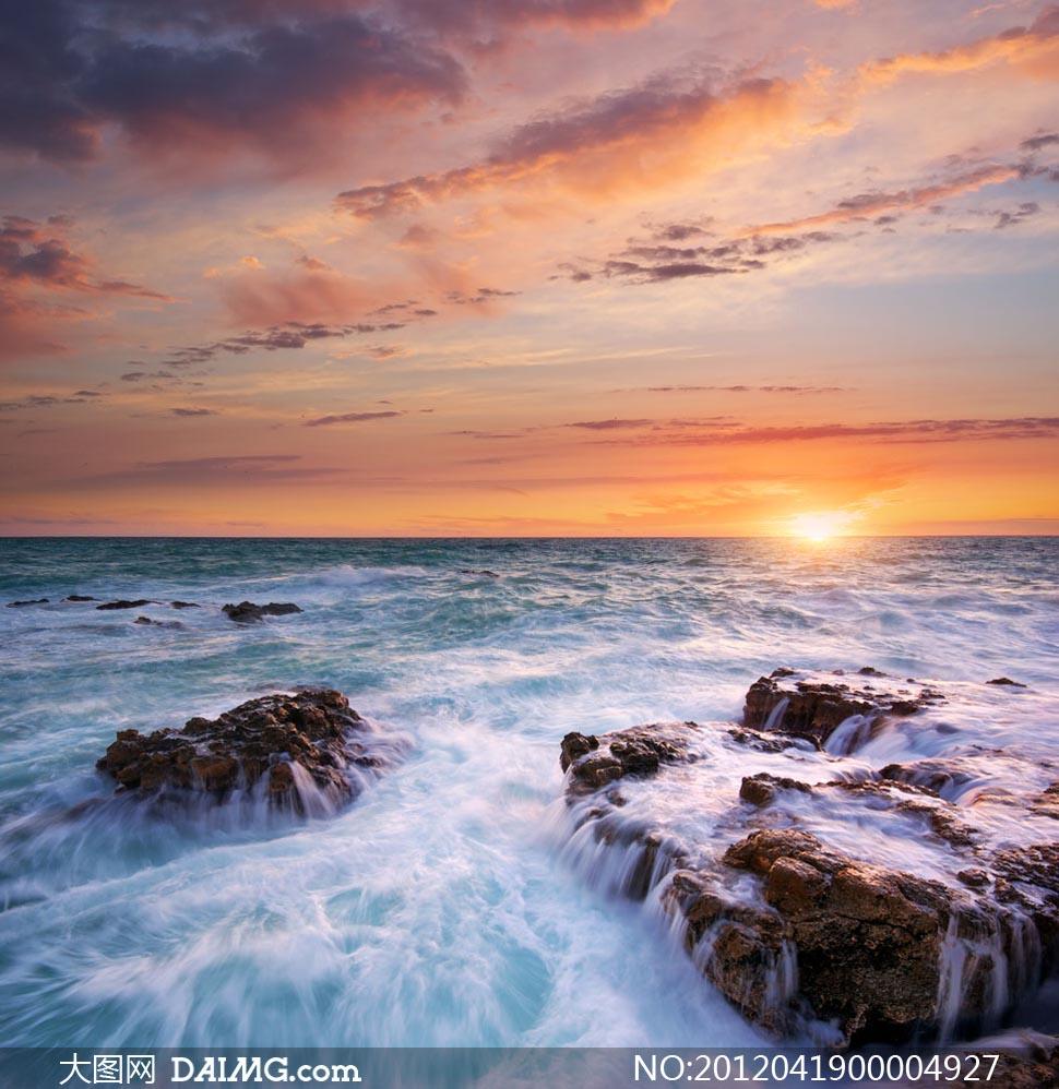 海上日出和海边岩石摄影图片