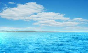 蓝天白云下的蓝色大海摄影图片