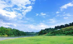 蓝天白云下的草地和河流摄影图片