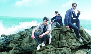 坐在礁石上三个男人摄影高清图片