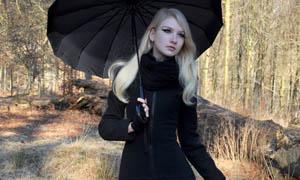 打着伞在公园散步的美女摄影图片