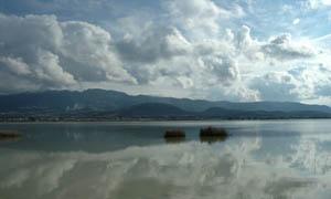 乌云下的山峰和湖面倒影摄影图片