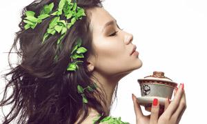 端着茶杯抬头思考的美女摄影图片