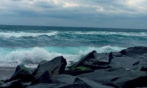 乌云下的海边浪花摄影图片
