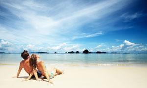 坐在沙滩上的情侣男女摄影高清图片