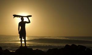黄昏海边的冲浪人物剪影高清图片