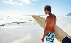 携冲浪板朝大海走去的男人高清图片