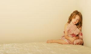 坐在墙角的抱熊小女孩摄影高清图片