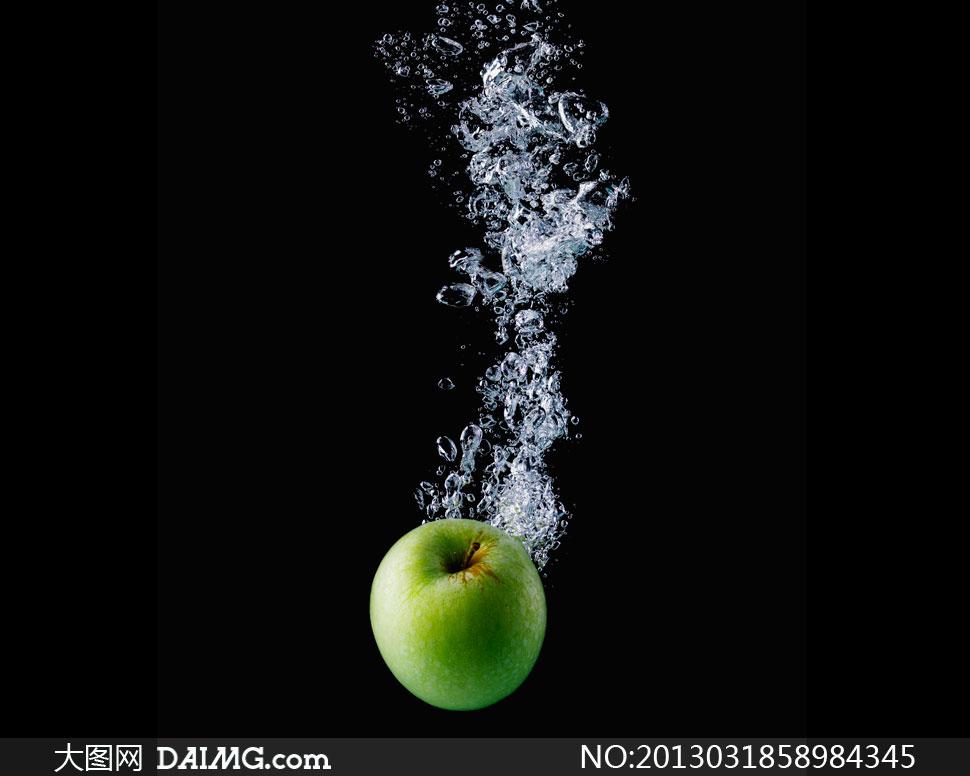 黑色背景青苹果与水花摄影高清图片