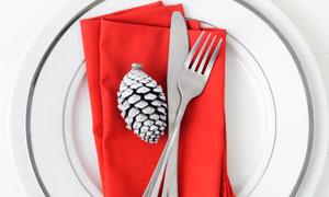 放在盘子里的餐布刀叉摄影高清图片