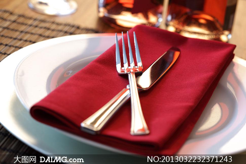 放盘子里的红色餐布与刀叉高清图片