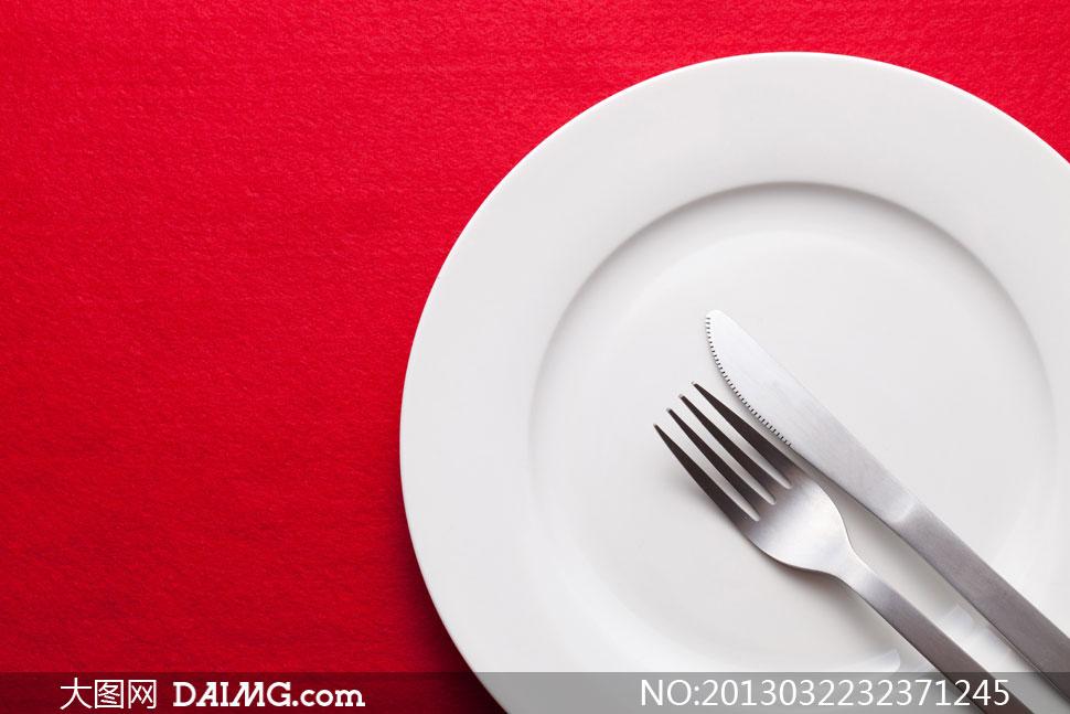 红色桌布白色盘子刀叉摄影高清图片