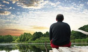 背着坐在木桥上看远方的男人图片素材
