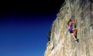 户外峭壁上攀岩的人物摄影高清图片