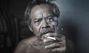 正在吸煙的皺紋老人攝影圖片
