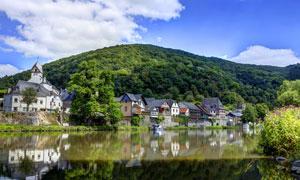 绿色山坡下的欧洲小镇摄影图片