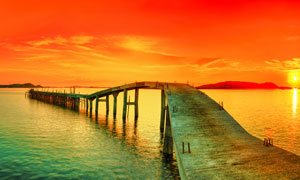 日落黄昏海边木桥摄影图片