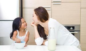 厨房里吃饭互动的母女摄影高清图片