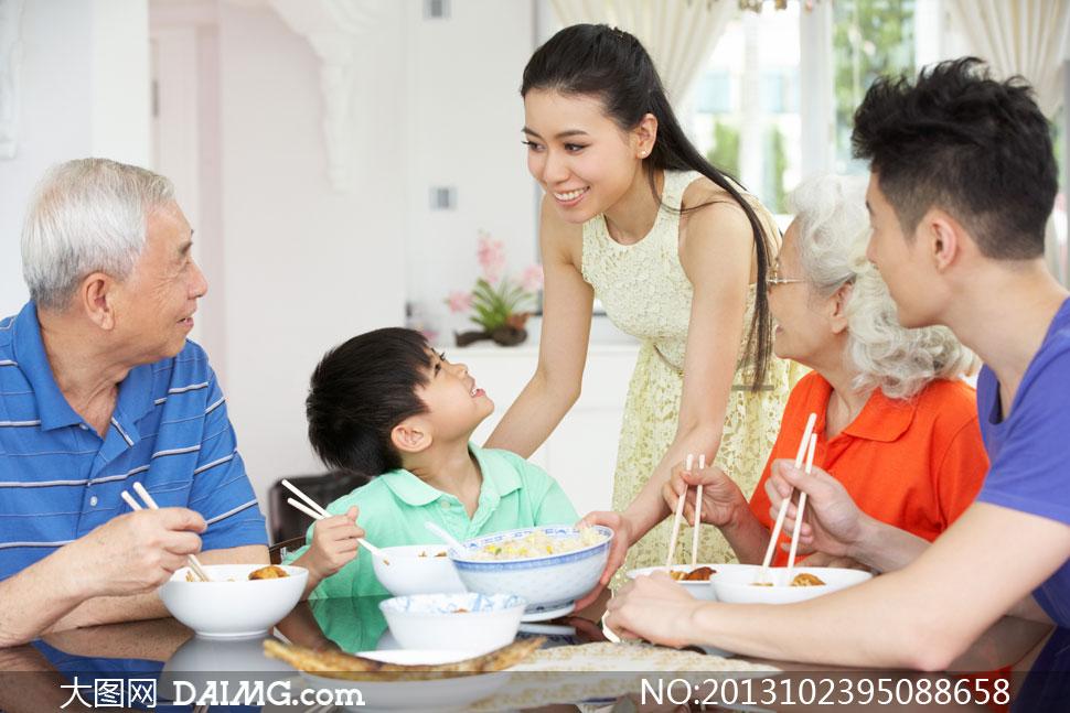 在饭桌上吃饭的一家人摄影高清图片