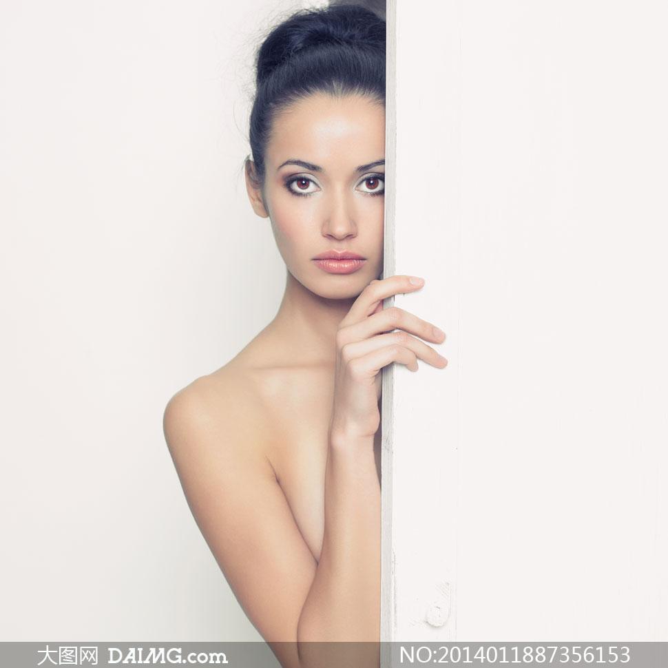 躲藏在门后的盘发美女摄影高清图片