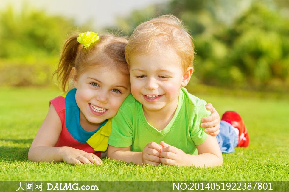 趴在草地上的两个小孩摄影高清图片