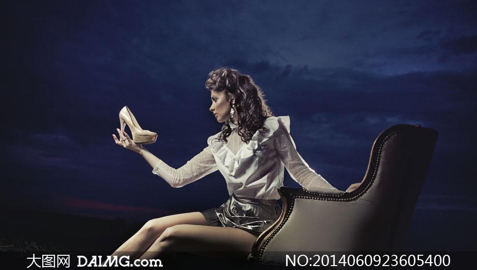 对着高跟鞋端详的美女摄影高清图片
