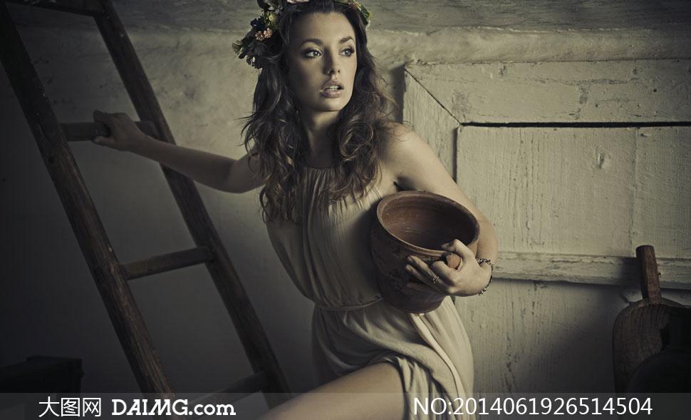 抱着陶罐爬梯子的美女摄影高清图片