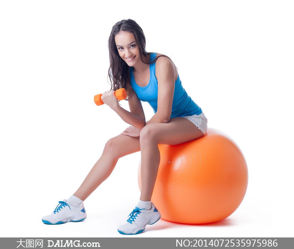 在橙色健身球上的美女摄影高清图片图片
