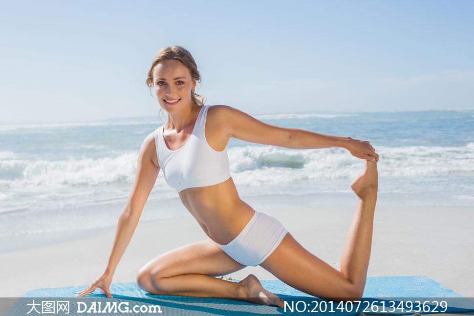 海边在瑜伽垫上的美女摄影高清图片