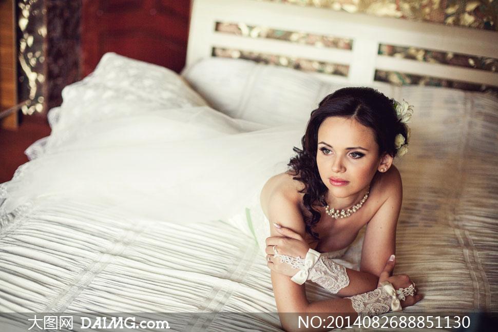 趴床上的白色婚纱美女摄影高清图片