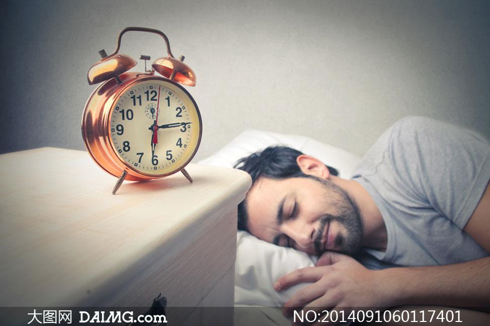 闹钟与躺着睡觉的男人摄影高清图片