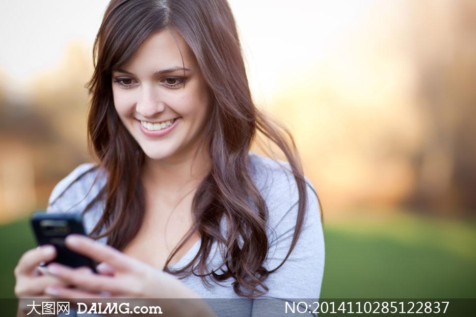 高清摄影大图图片素材人物美女女人女性长发秀发笑容开心卷发玩手机