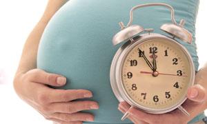 手拿着闹钟的孕妇腹部特写高清图片