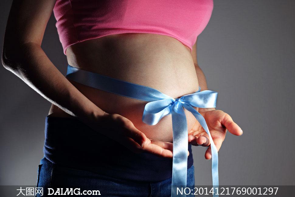 腹部系着蓝丝带的孕妇摄影高清图片